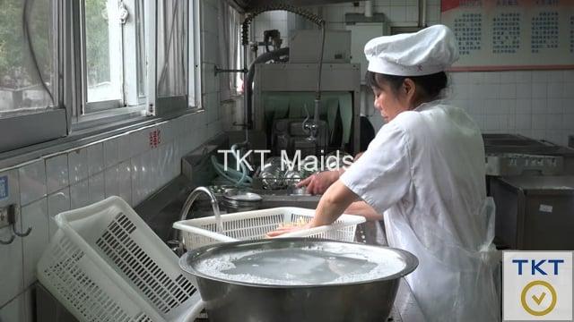 nhân viên tạp vụ rửa chén tại khu bếp nhà hàng